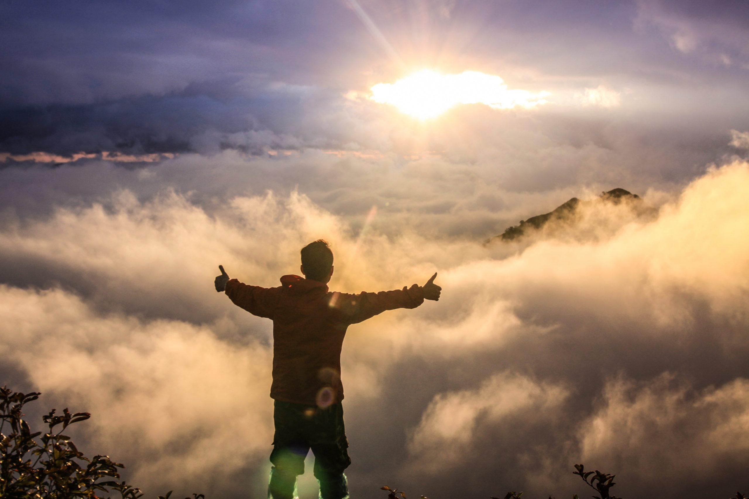 Mann mit Armen ausgestreckt und beiden Daumen nach oben steht an einer Lichtung über den Wolken