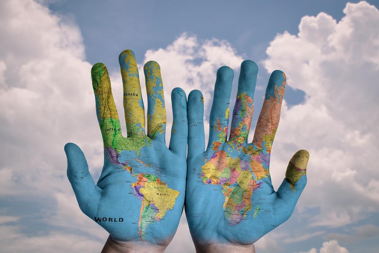 Hände mit Weltkarte aufgedruckt vor dem himmel
